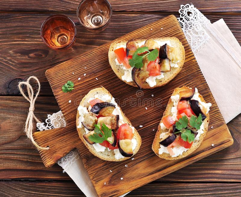 Crostini met zachte kaas, aubergine, tomaten en knoflook royalty-vrije stock fotografie