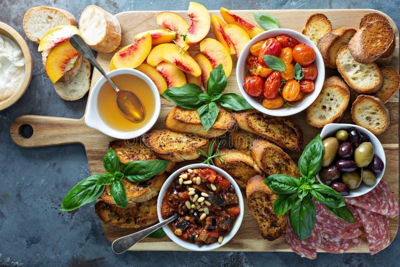 Crostiniraad met tomaten, perziken en onderdompeling stock afbeeldingen