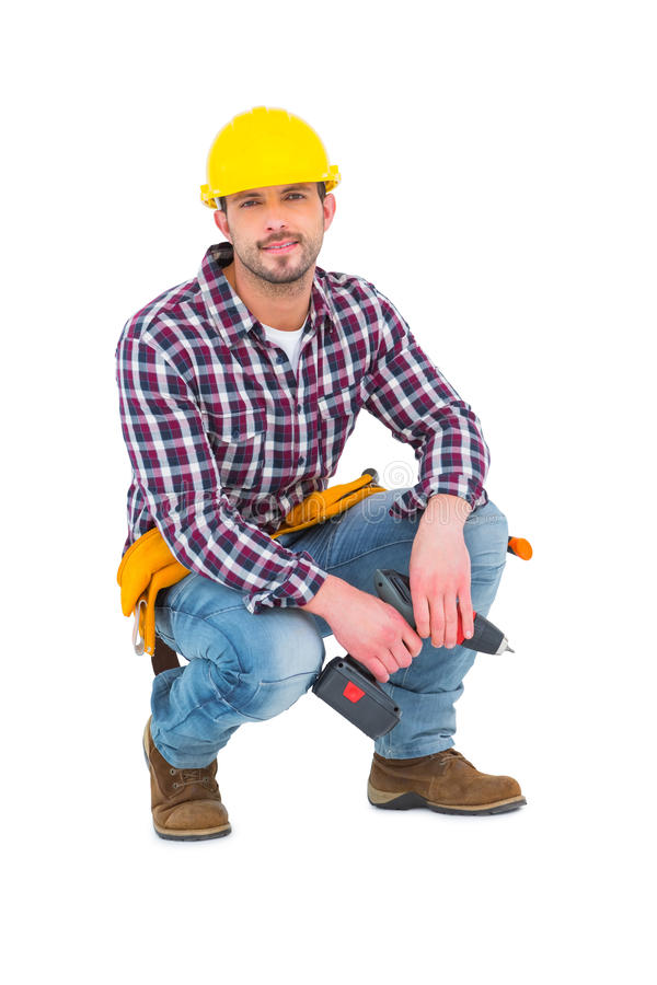 Crouching handyman holding power drill. On white background royalty free stock image