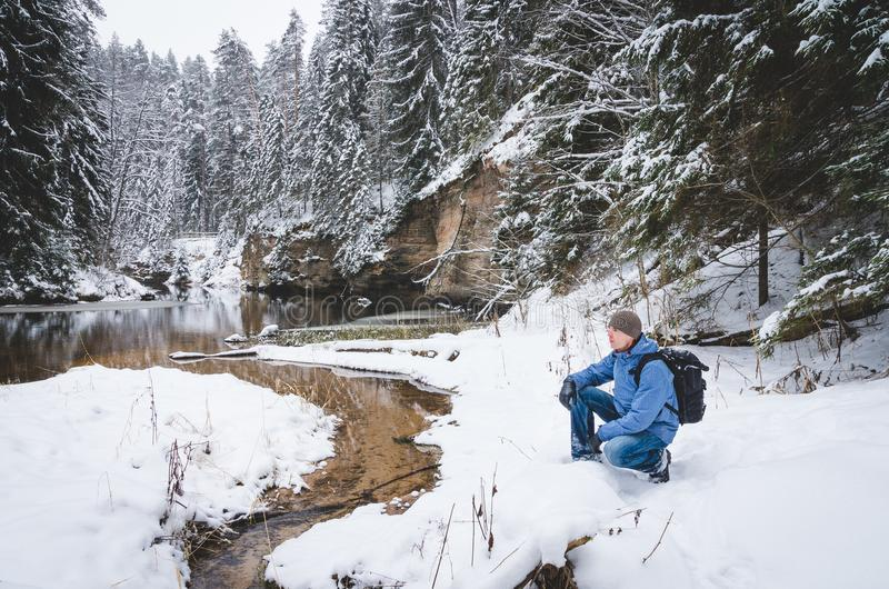 A crouching hiker by the winter river vol2. A crouching hiker by the winter river with steep banks and snowy forest royalty free stock image
