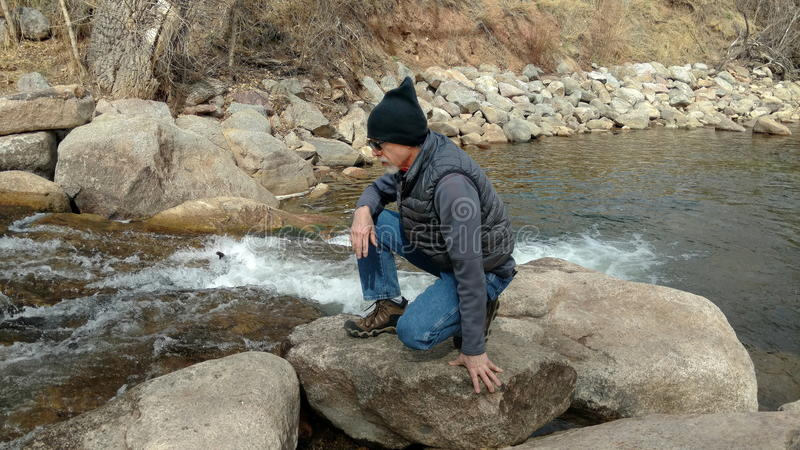 Crouching Man Studying A Stream royalty free stock image