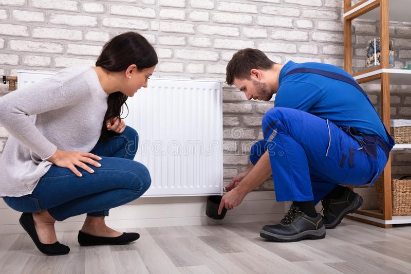 Serviceman Turning Radiator Bleed Valve To Release Air. Crouching Woman With Serviceman Turning Radiator Bleed Valve To Release Air With Cup royalty free stock image