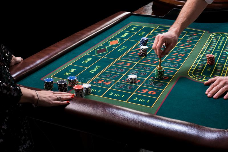 Crouoier atrás da tabela de jogo em um casino imagem de stock royalty free