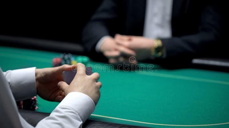 Crouoier masculino que baralha cartões no casino, pronto para começar o jogo de pôquer com cliente foto de stock