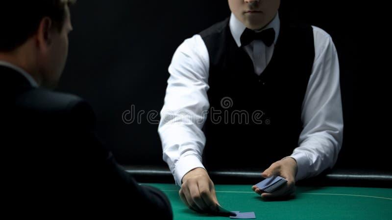 Crouoier sério do casino que negocia os cartões para o cliente na tabela verde do pôquer, jogando fotos de stock royalty free