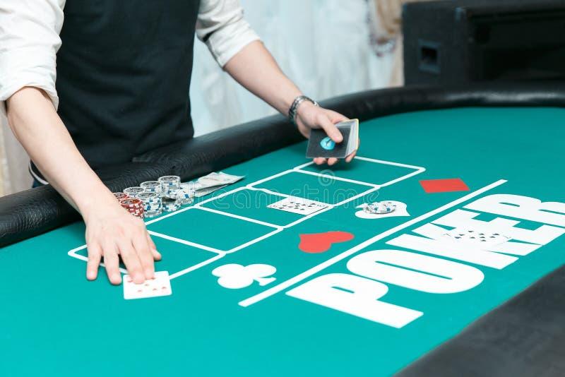 Croupier à la table de tisonnier dans le casino Puces et cartes sur la table photo stock