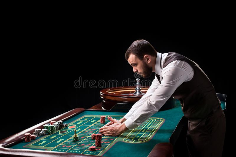 Croupier bak dobbleritabellen i en kasino royaltyfri foto