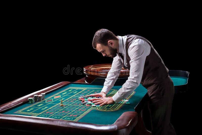 Croupier bak dobbleritabellen i en kasino royaltyfri bild