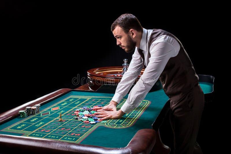 Croupier bak dobbleritabellen i en kasino arkivbilder