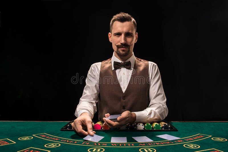 Croupier bak dobbleritabellen i en kasino arkivfoto
