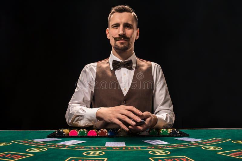 Croupier bak dobbleritabellen i en kasino royaltyfria bilder