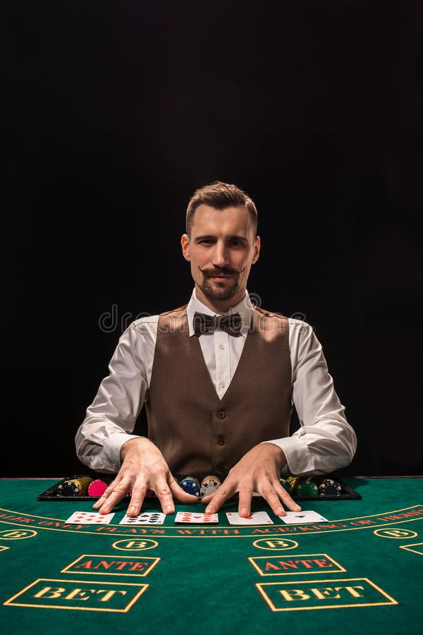 Croupier bak dobbleritabellen i en kasino royaltyfri fotografi