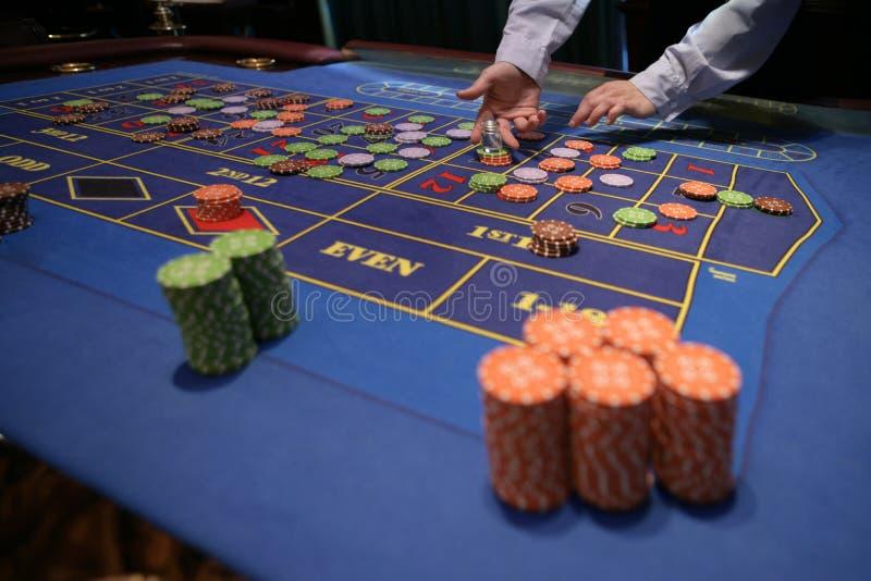 Croupier bak dobbleritabellen i en kasino royaltyfria foton