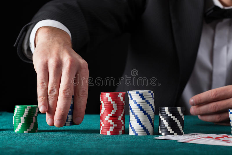Croupier in casino. Croupier chip tricks on green casino table royalty free stock photo