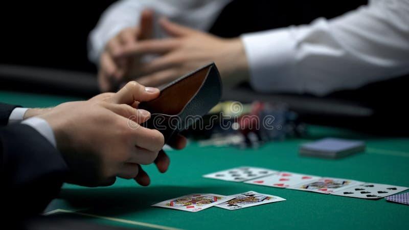 Croupier, das alle Chips und Geld, umgekippten Pokerspieler zeigt leere Geldbörse nimmt stockfotos