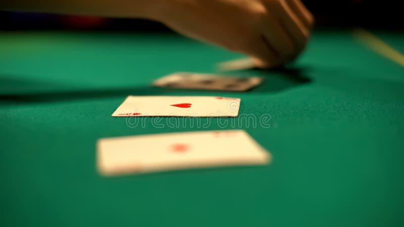 Croupier, das Karten auf Tabellen-, Sch?rhaken- und Blackjackkasinospielen, Verm?gen ausbreitet lizenzfreie stockfotos