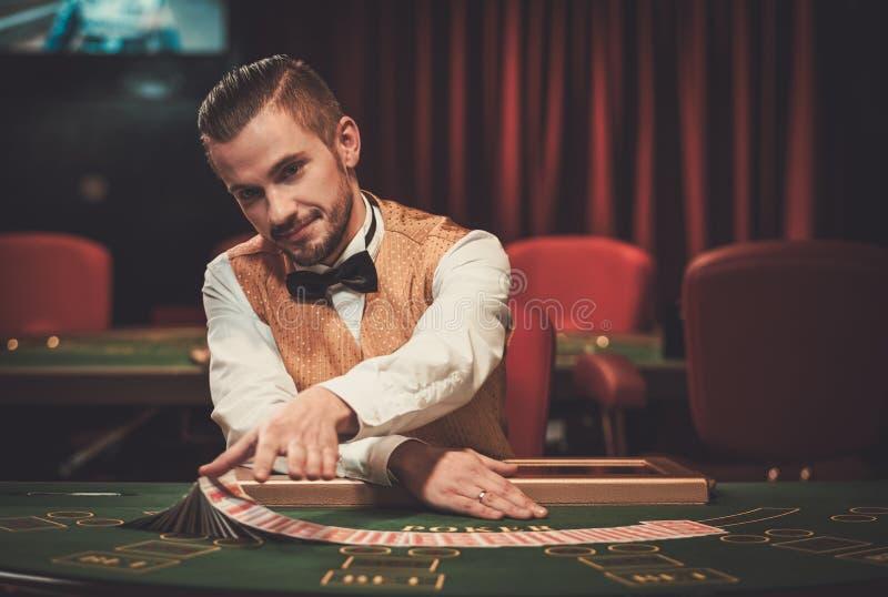 Croupier hinter Spieltisch in einem Kasino lizenzfreie stockfotos