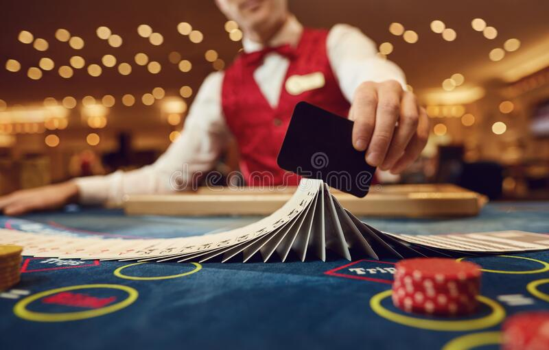 Croupier holds poker cards in his hands at a table in a casino. The croupier holds poker cards in his hands at a table in a casino stock photo