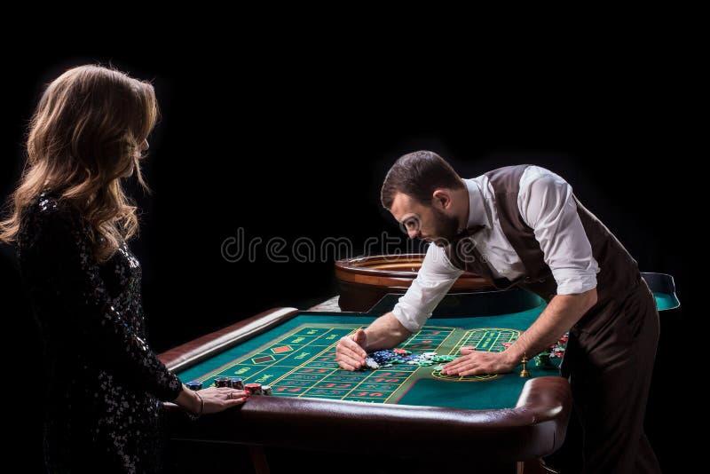 Croupier- och kvinnaspelare på en tabell i en kasino Bild av A.C. royaltyfri fotografi