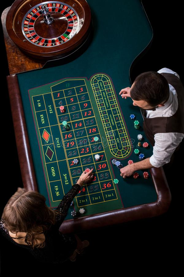Croupier- och kvinnaspelare på en tabell i en kasino Bild av A.C. royaltyfria foton