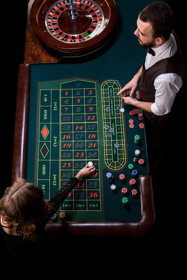 Croupier- och kvinnaspelare på en tabell i en kasino Bild av A.C. royaltyfri foto