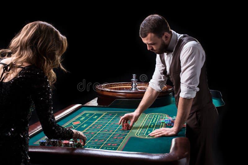 Croupier- och kvinnaspelare på en tabell i en kasino Bild av A.C. royaltyfri bild