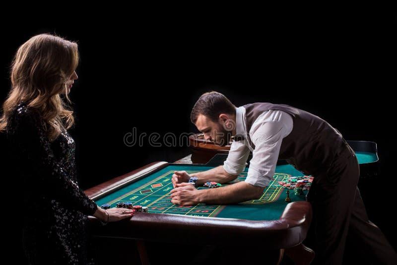 Croupier- och kvinnaspelare på en tabell i en kasino Bild av A.C. arkivfoto