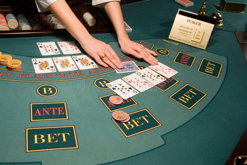 Croupier que segura cartões na tabela do póquer foto de stock