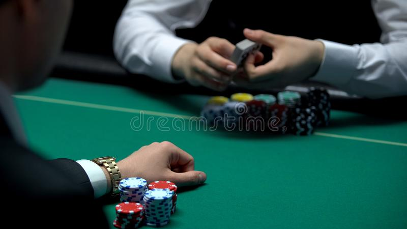 Croupier ready to deal cards for businessman playing poker at casino, gambling stock photo