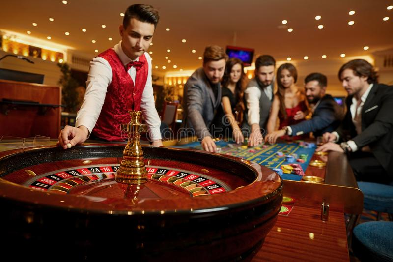 Croupier rymmer en roulettboll i en kasino i hans hand royaltyfria bilder