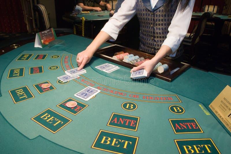 Croupier traitant des cartes à la table de tisonnier photographie stock