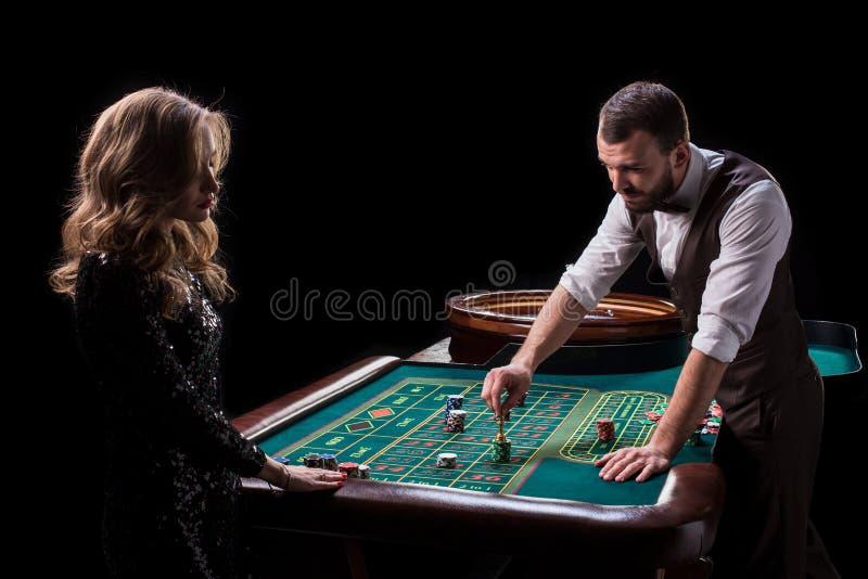 Croupier- und Frauenspieler an einem Tisch in einem Kasino Bild von Wechselstrom stockfotos