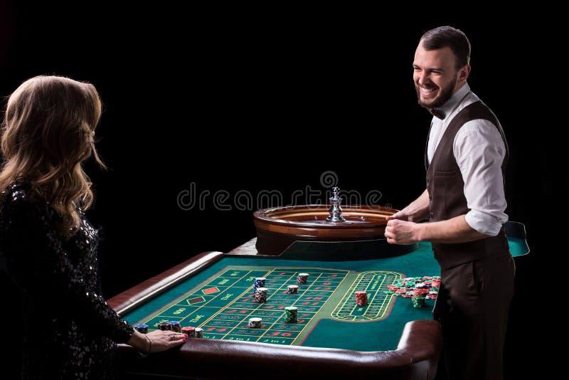 Croupier- und Frauenspieler an einem Tisch in einem Kasino Bild von Wechselstrom lizenzfreie stockfotografie