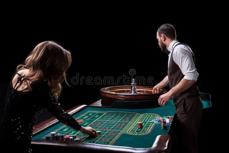 Croupier- und Frauenspieler an einem Tisch in einem Kasino Bild von Wechselstrom lizenzfreies stockbild