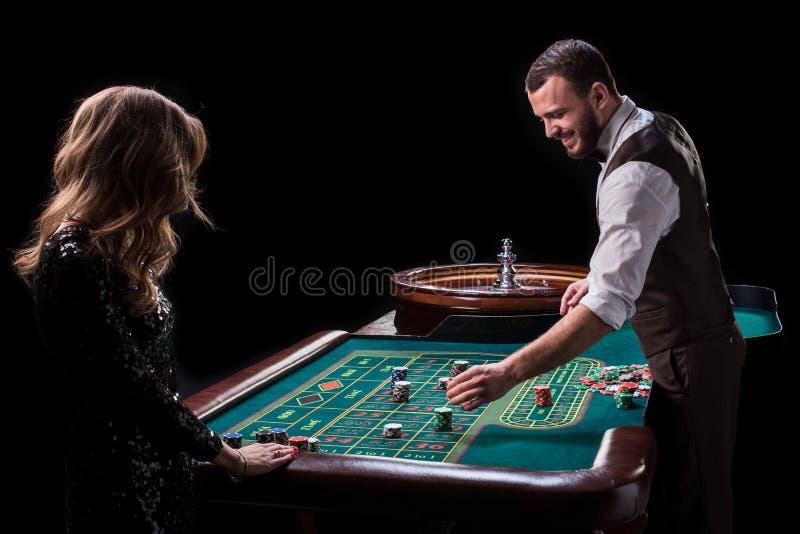 Croupier- und Frauenspieler an einem Tisch in einem Kasino Bild von Wechselstrom stockfotografie