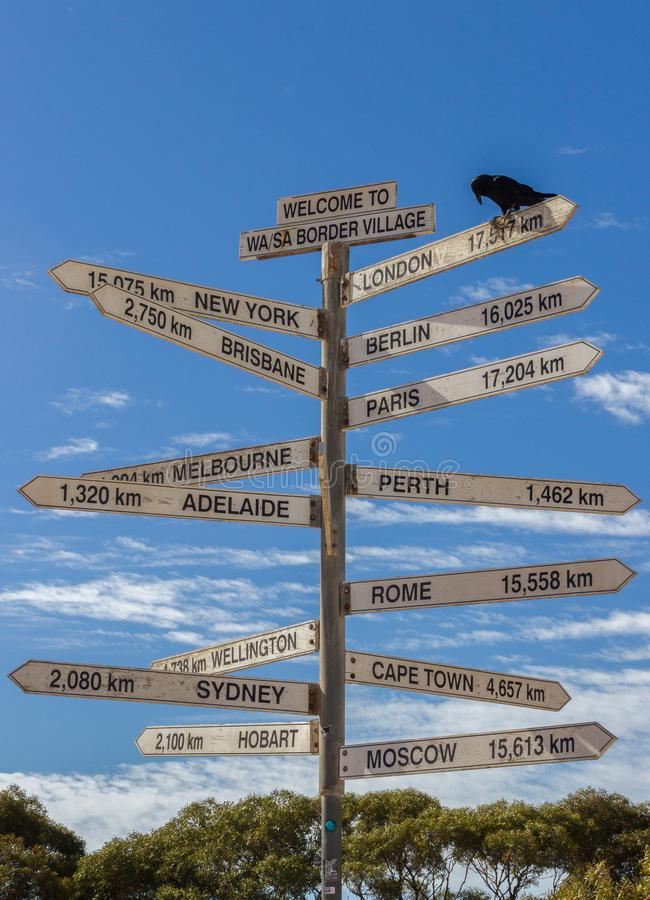 Crow sitting on a Milestone sign in the Nullabor dessert, Australia stock images