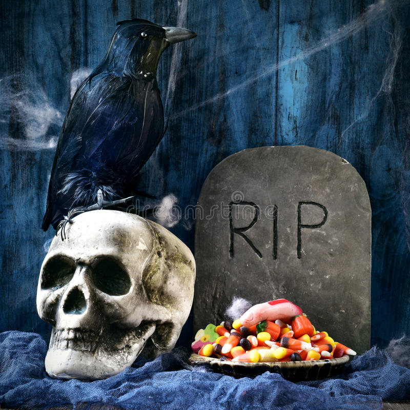 Crow, skull, gravestone and Halloween candies. A plate with Halloween candies and an amputated finger in a dismal scene with a crow, a skull and a gravestone stock photos