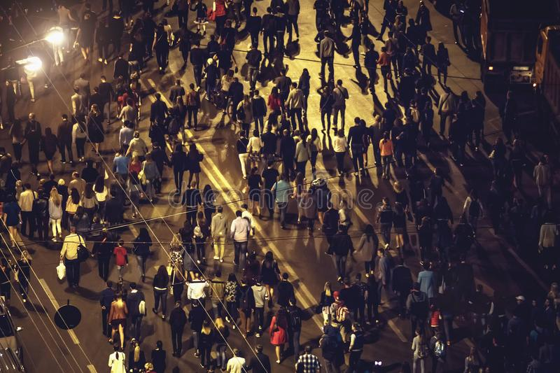 Crowd of anonymous people walking on night Voronezh street royalty free stock photography