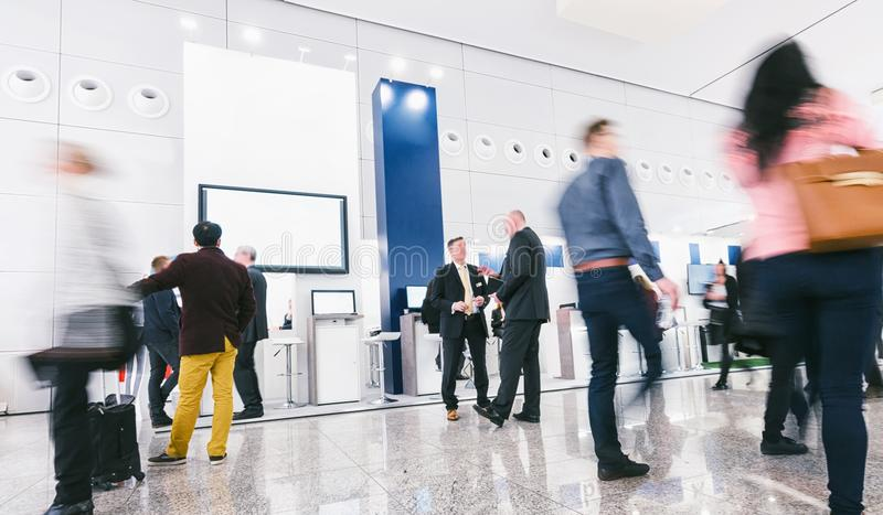 Crowd of business people at a trade show booth. Crowd of trade show visitors walking on a trade show. ideal for websites and magazines layouts stock image