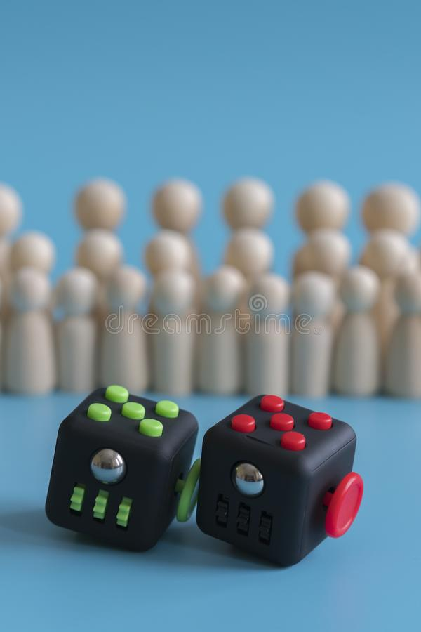 Crowd calm concept. answer how to calm the crowd. Cube stress reliever and wooden figures on a blue background. vertical photo stock photo