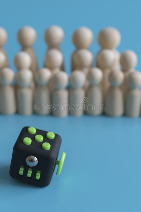 Crowd calm concept. answer how to calm the crowd. Fidget Cube stress reliever and wooden figures on a blue background. vertical stock image