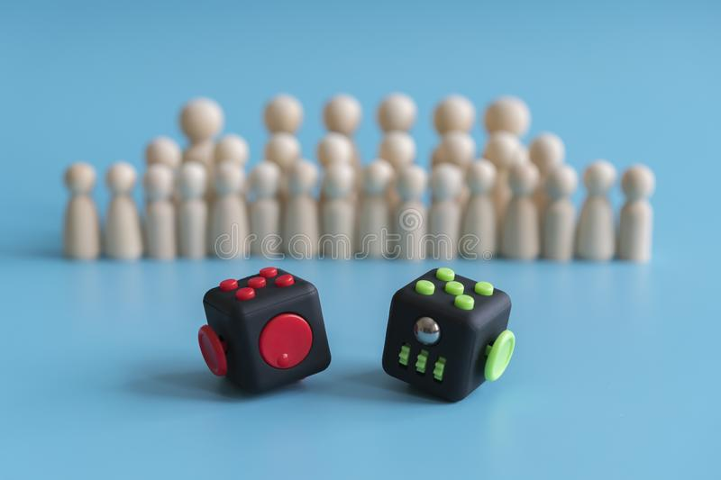 Crowd calm concept. Cube stress reliever and wooden figures on a blue background.  stock photos
