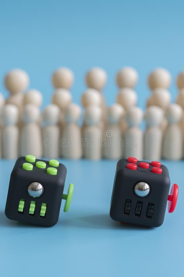 Crowd calm concept. Cube stress reliever and wooden figures on a blue background. vertical photo.  stock images