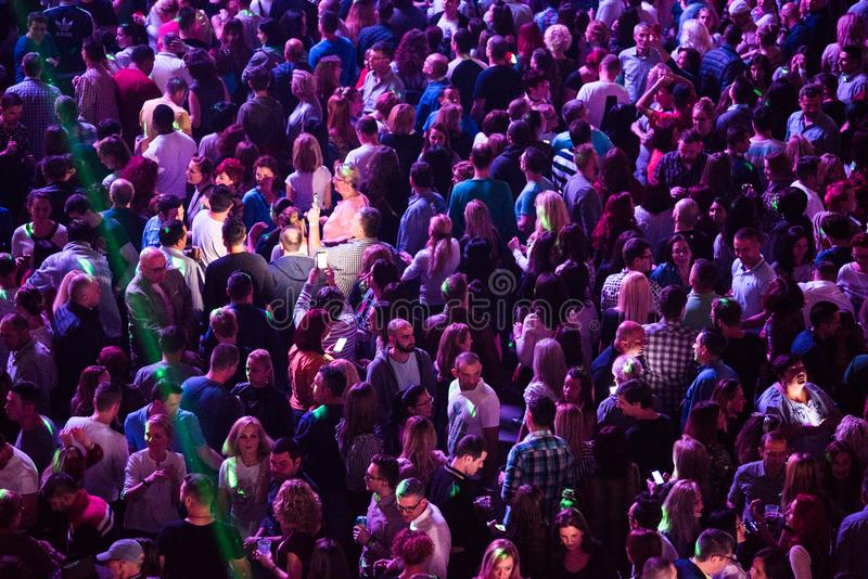 Crowd of cheerful people partying at a live concert. CLUJ NAPOCA, ROMANIA - NOVEMBER 19, 2017: Crowd of cheerful people dancing and partying during the We Love royalty free stock photography