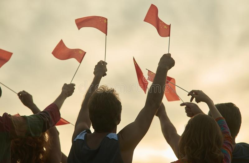 Crowd with chineese flags. People raising small chineese flags, back view stock image