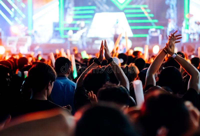 Crowd clap or hands up at concert stage lights. And people fan audience silhouette raising hands in the music festival rear view with spotlights glowing effect stock photos