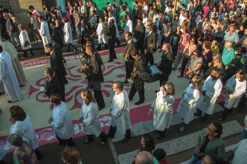 Crowd on a colorful sand carpet at the Holy Week. Sao Manuel, Brazil - May 31, 2018. Crowd with religious procession passing by a colorful sand carpet at the stock image