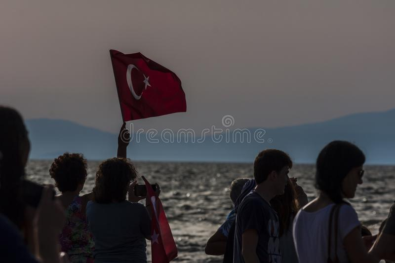 Crowd commemorating Izmir liberation from greeks. During sunset crowd is commemorating the liberation of Izmir from greeks. A woman is holding a turkish flag stock photos