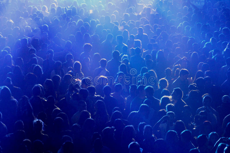 Crowd at concert or party. People at concert or show, all together, party having fun, happy, night, drinking with friends. Blue lights, dark environment, against stock image