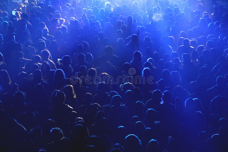 Crowd at concert or party. People at concert or show, all together, party having fun, happy, night, drinking with friends. Blue lights, dark environment, against royalty free stock image